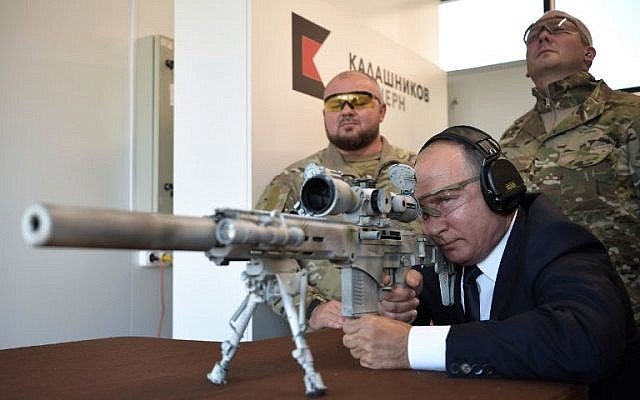 Russian President Vladimir Putin looks through the scope as he shoots a Chukavin sniper rifle (SVC-380) during a visit to the military Patriot Park in Kubinka, outside Moscow, on September 19, 2018. (AFP/ SPUTNIK / Alexey NIKOLSKY)