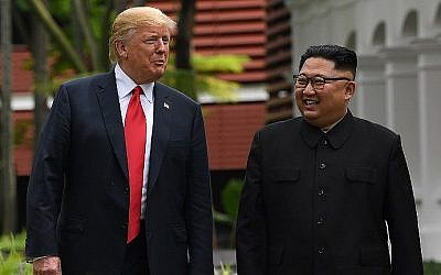In this file photo taken on June 11, 2018, North Korean strongman Kim Jong Un, right, walks with US President Donald Trump, left, during a break in talks at their summit meeting on Sentosa island in Singapore. (AFP /Saul Loeb)
