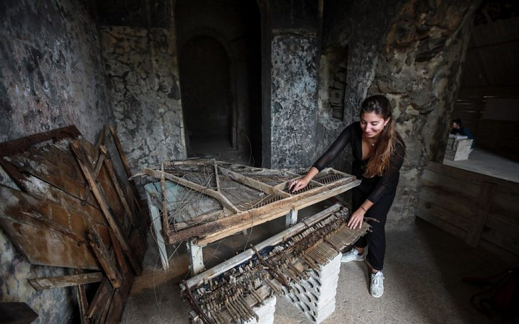 This picture taken on September 21, 2018, shows a woman touching the remains of a destroyed piano in a room at the Sofar Grand Hotel in the Lebanese village of Sofar, some 30 kilometers (20 miles) east of Beirut. (AFP PHOTO / ANWAR AMRO)