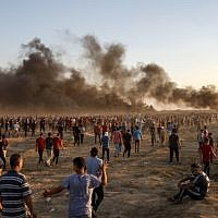 Palestinian protesters gather during a demonstration along the Israeli border fence east of Gaza City on September 21, 2018 as smoke plumes billow from burning tires in the background. (AFP/Said Khatib)