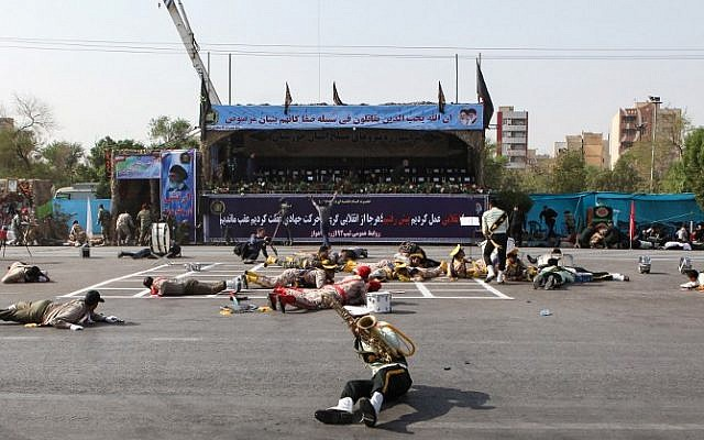 This picture taken on September 22, 2018 in the southwestern Iranian city of Ahvaz shows injured soldiers lying on the ground at the scene of an attack on a military parade that was marking the anniversary of the outbreak of its devastating 1980-1988 war with Saddam Hussein's Iraq. (AFP / ISNA / ALIREZA MOHAMMADI)