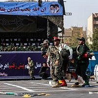 This picture taken on September 22, 2018, in the southwestern Iranian city of Ahvaz shows Iranian soldiers carrying away an injured colleague at the scene of an attack on a military parade that was marking the anniversary of the outbreak of its devastating 1980-1988 war with Saddam Hussein's Iraq. (AFP/ ISNA / MORTEZA JABERIAN)
