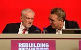 Britain's opposition Labour Party leader Jeremy Corbyn (L) chats with Tom Watson deputy leader of Britain's opposition Labour Party on stage at the Labour Party Conference in Liverpool, England on September 23, 2018, the official opening day of the annual Labour Party Conference. (AFP PHOTO / Paul ELLIS)