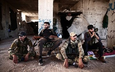 Fighters from the Nureddine al-Zinki unit, a moderate Syrian opposition faction affiliated with the Muslim Brotherhood and made up of former Syrian Free Army fighters, rest in a position in a rebel-held part of Aleppo province that lies directly east of the main opposition bastion in Idlib on September 23, 2018 (AFP PHOTO / Nazeer AL-KHATIB)