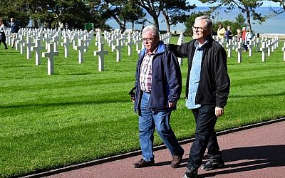 Andre Gantois (L), 72, a resident of Ludres, in eastern France, and Allen Henderson, 65, of Greenville, South Carolina, walk past graves at the Normandy American Cemetery and Memorial on September 24, 2018, in Colleville-sur-Mer. (AFP PHOTO / Damien MEYER)