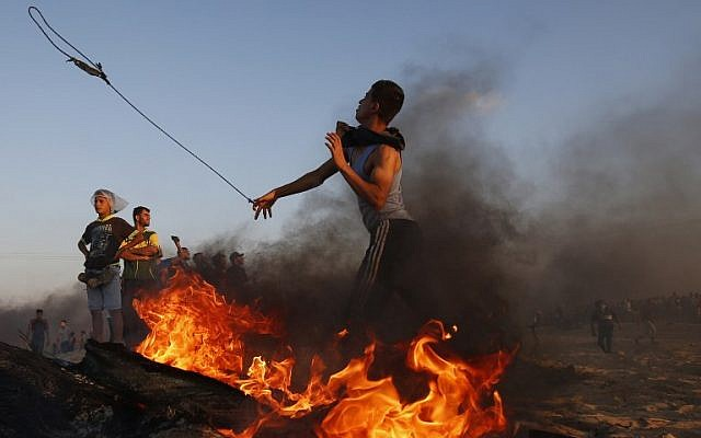 A Palestinian demonstrator uses a slingshot to throw stones during a protest on the Gaza-Israel border on September 24, 2018. (AFP PHOTO / SAID KHATIB)