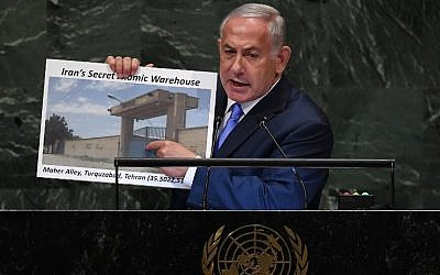"Prime Minister Benjamin Netanyahu addresses the General Assembly at the United Nations in New York on September 27, 2018, holding up a picture of an alleged Iranian ""secret atomic warehouse."" (Timothy A. Clary/AFP)"