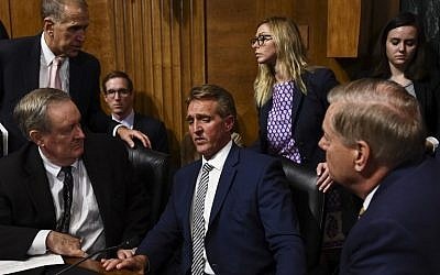 Senate Judiciary Committee member Senator Jeff Flake, center, speaks with colleagues after a hearing on Capitol Hill in Washington, DC on September 28, 2018. (AFP/Brendan Smialowski)