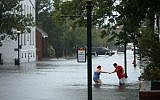 Shianne Coleman (L) gets a hand from friend Austin Gremmel as they walk in flooded streets as the Neuse River begins to flood its banks during Hurricane Florence September 13, 2018 in New Bern, North Carolina.(Chip Somodevilla/Getty Images/AFP