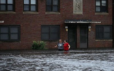 Residents wade through deep floodwater to retrieve belongings from the Trent Court public housing apartments after the Neuse River went over its banks during Hurricane Florence September 13, 2018 in New Bern, United States. (Chip Somodevilla/Getty Images/AFP
