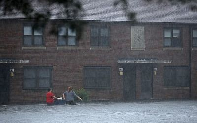 Residents wade through deep floodwater to retrieve belongings from the Trent Court public housing apartments after the Neuse River went over its banks during Hurricane Florence September 13, 2018 in New Bern, United States. (Chip Somodevilla/Getty Images/AFP)