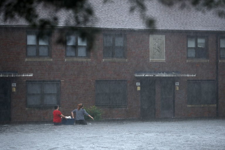 Residents wade through deep floodwater to retrieve belongings from the Trent Court public housing apartments after the Neuse River went over its banks during Hurricane Florence