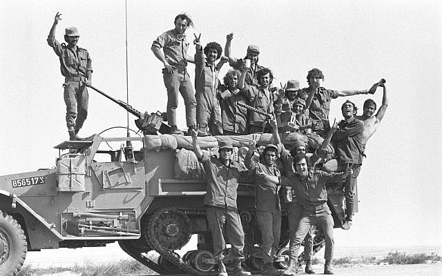 Soldiers pose on the top of a tank during the outbreak of the Yom Kippur War on October 6, 1973. (Bamahane/Defense Ministry Archives)