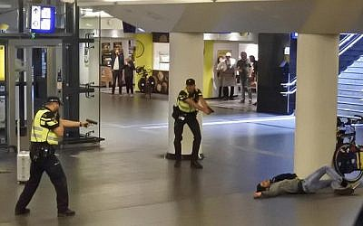 Dutch police officers point their guns at a wounded 19-year-old man, who was shot by police after stabbing two people in the central railway station, in Amsterdam, the Netherlands, August 31, 2018. (AP Photo)