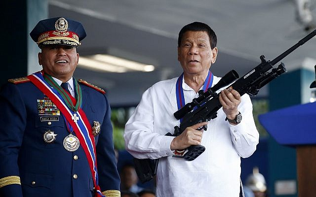 "Philippine President Rodrigo Duterte, right, jokes to photographers as he holds an Israeli-made Galil rifle which was presented to him by former Philippine National Police Chief Director General Ronald ""Bato"" Dela Rosa at the turnover-of-command ceremony at the Camp Crame in Quezon city northeast of Manila, April 19, 2018. (Bullit Marquez/AP)"