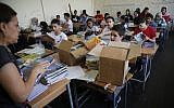 Palestinian students receive new studying books inside their classroom, during the first day of a new school year, at one of the UNRWA schools, in Beirut, Lebanon, September 3, 2018. (Hussein Malla/AP)