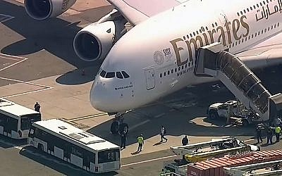 In this frame from video, a person walks off an Emirates plane at JFK International Airport to a waiting bus on September 5, 2018, in New York, as emergency response crews gather outside the plane amid reports of ill passengers aboard a flight from Dubai. (WABC 7 via AP)