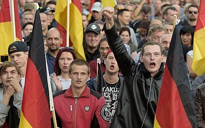 People attend a demonstration in Chemnitz, eastern Germany, on September 7, 2018, after several nationalist groups called for marches protesting the killing of a German man two weeks ago, allegedly by migrants from Syria and Iraq. (AP Photo/Jens Meyer)