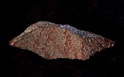 This undated photo provided by Craig Foster in September 2018 shows a drawing made with ochre pigment on silcrete stone, found in the Blombos Cave east of Cape Town, South Africa. (Craig Foster via AP)
