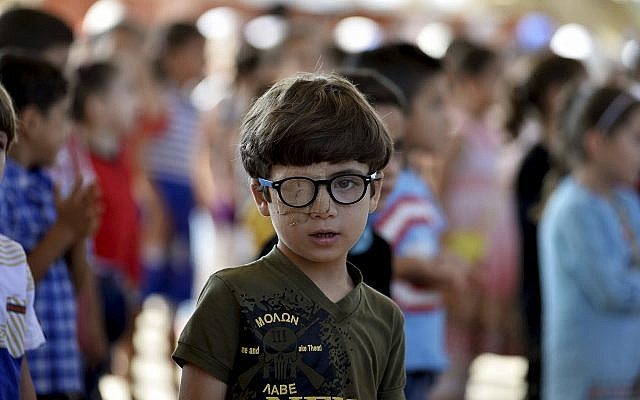 In this Tuesday, September 11, 2018 photo, Muhammed Halife, 5, who was injured during a bombing, stands at his school in the northern town of Jisr al-Shughur, Syria, west of the city of Idlib. (Ugur Can/DHA via AP)