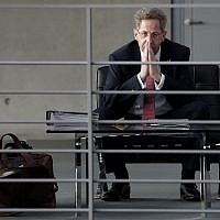 In this Wednesday, Sept. 12, 2018 photo Hans-Georg Maassen, center, head of the German Federal Office for the Protection of the Constitution, waits for the beginning of a hearing at the home affairs committee of the German federal parliament, Bundestag, in Berlin, Germany.  (AP Photo/Michael Sohn)