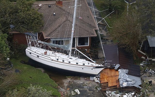 A sailboat is shoved up against a house and a collapsed garage Saturday, September 15, 2018, after heavy wind and rain from Florence, now a tropical storm, blew through New Bern, North Carolina. (AP Photo/Steve Helber)