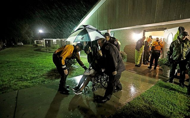 Members of the Nebraska Task Force 1 urban search and rescue team help load an elderly resident onto a bus as they evacuate an assisted living facility to a church as a precaution against potential flooding the city could see from tropical storm Florence in Fayetteville, North Carolina, Saturday, September 15, 2018. (AP Photo/David Goldman)