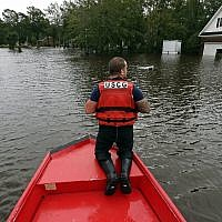 Petty Officer Second Class David Kelley patrols a flooded neighborhood in Lumberton, North Carolina, September 16, 2018, following flooding from Hurricane Florence. (AP Photo/ Gerry Broome)