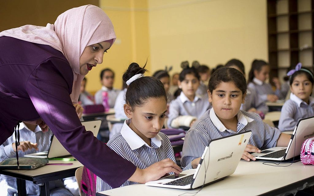 Illustrative: Palestinian children use laptops at the Ziad Abu Ein School in the West Bank city of Ramallah, September 8, 2018 (AP Photo/Majdi Mohammed)