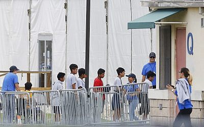 In this June 20, 2018, photo, Immigrant children walk in a line outside the Homestead Temporary Shelter for Unaccompanied Children a former Job Corps site that now houses them in Homestead, Florida. (AP Photo/Brynn Anderson)