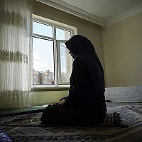 In this August 20, 2018, photo, Meripet, 29, prays at her home in Istanbul, Turkey. Meripet came to Turkey in February 2017 to visit her sick father, leaving four children behind. (AP Photo/Dake Kang)