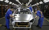 In this Sunday, September 9, 2018 photo, workers wipe the body of a car at the Iran Khodro automobile manufacturing plant just outside Tehran, Iran. (AP Photo/Ebrahim Noroozi)
