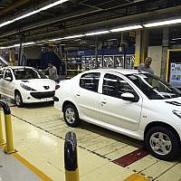 In this September 9, 2018, photo, a line of Peugeot cars rolls out at the state-run Iran Khodro automobile manufacturing plant, just outside Tehran, Iran. (AP Photo/Ebrahim Noroozi)