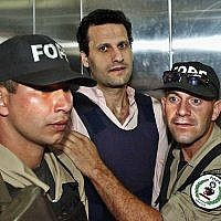 In this Nov. 17, 2003 file photo, Lebanese citizen Assad Ahmad Barakat, who was then facing tax evasion charges, is escorted by police to a courthouse in Asuncion, Paraguay. On Friday, Sept. 21, 2018, federal police in Brazil arrested Barakat, a fugitive accused of belonging to Lebanon's Hezbollah militia and of being a key financier of terrorism.  (AP Photo/Jorge Saenz)
