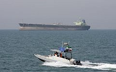 In this July 2, 2012, photo, an Iranian Revolutionary Guard speedboat moves in the Persian Gulf while an oil tanker is seen in the background (AP Photo/Vahid Salemi)