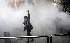 In this Dec. 30, 2017 file photo, taken by an individual not employed by the Associated Press and obtained by the AP outside Iran, a university student attends a protest inside Tehran University while a smoke grenade is thrown by anti-riot Iranian police, in Tehran, Iran (AP Photo, File)