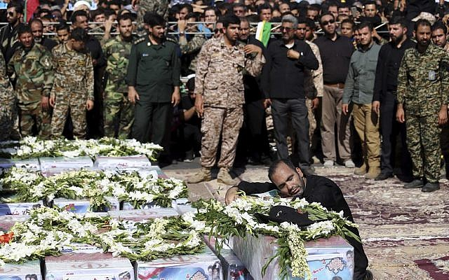 Father of Mohammad Taha Eghadami, a 4-year-old boy who was killed in Saturday's terror attack on a military parade, mourns over his coffin during a mass funeral ceremony for the victims, in southwestern city of Ahvaz, Iran, Monday, Sept. 24, 2018 (AP Photo/Ebrahim Noroozi)
