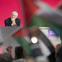 UK Labour leader Jeremy Corbyn sits on stage as supporters wave Palestinian flags during the party's annual conference in Liverpool, England, on September 25, 2018. (Stefan Rousseau/PA via AP)