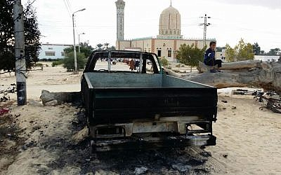 In this November 25, 2017 file photo, a burned truck remains outside the Al-Rawda Mosque a day after attackers killed hundreds of worshipers, in Bir al-Abd northern Sinai, Egypt. (AP Photo/Tarek Samy)