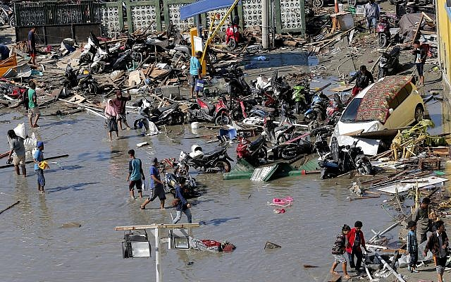 People outside a shopping mall damaged in earthquakes and a tsunami in Palu, Central Sulawesi, Indonesia, Sunday, Sept. 30, 2018. (AP Photo/Tatan Syuflana)