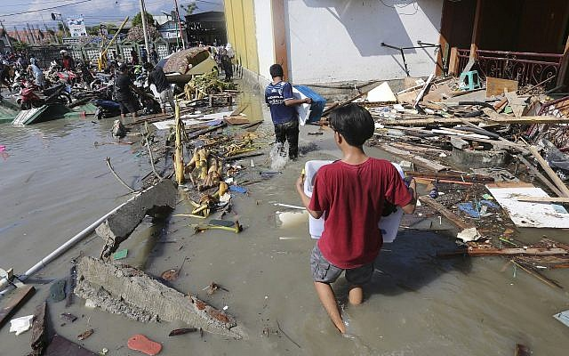 People carry items looted from a shopping mall badly damaged by a massive earthquake and tsunami in Palu, Central Sulawesi, Indonesia, Sunday, Sept. 30, 2018. (AP Photo/Tatan Syuflana)