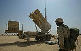 Capt. Issac Gipson of Biloxi, Mississippi, stands in front of a Patriot missile battery of the 5th Bat. 52nd Regiment of Air Defense Artillery at Camp New Jersey in the Kuwaiti desert, March 17, 2003.  (AP/Jean-Marc Bouju)