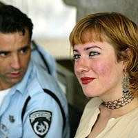British freelance journalist and activist Ewa Jasiewicz, right, sits next to an Israeli policeman  before a hearing in her deportation case at Tel Aviv's District Court, Israel Wednesday Aug. 18, 2004(AP Photo/Ariel Schalit)