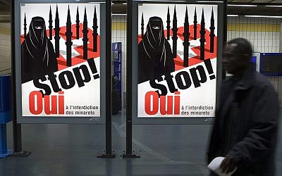 n this Nov. 4, 2009 file photo a man passes by a poster of the right-wing Swiss People's Party (SVP/UDC) which shows a woman wearing a burqa against a background of a Swiss flag upon which several minarets resemble missiles at the central station in Geneva, Switzerland. (AP Photo/Keystone, Salvatore Di Nolfi,)
