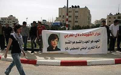 In this photo from March 11, 2010, Palestinians hold a banner displaying a picture of Palestinian Dalal Mughrabi, a Palestinian terrorist who killed dozens of Israeli civilians in a 1978 bus hijacking in Israel, seen in portrait, as they protest in the West Bank city of Ramallah. (AP Photo/Majdi Mohammed)