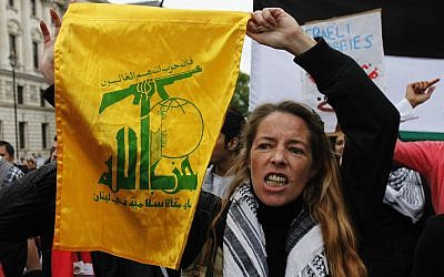 A pro-Palestinian supporter holds up a flag belonging to the Hezbollah group, during a march to protest against Israel in central London, May 31, 2010. (AP Photo/Lefteris Pitarakis)