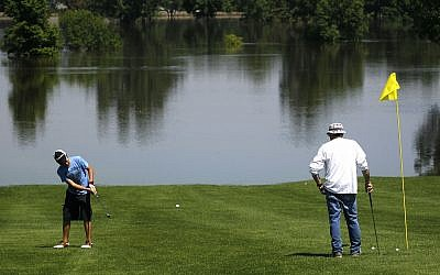 Ty Jones, left, and Bob Mehl, patrons of the Souris Valley Golf Course, play off a modified green on the 18 hole course shortened to nine by the rising Souris River Thursday, June 23, 2011 in Minot, N.D., (Illustrative photo: AP/Charles Rex Arbogast)