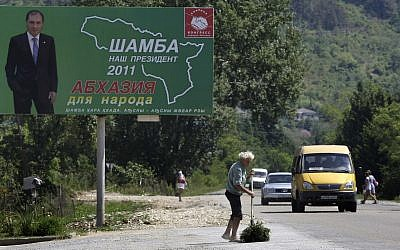 A man sweeps the road near a poster of one of three presidential candidates Sergei Shamba's in Sukhumi capital of Georgian breakaway region of Abkhazia, Wednesday, August 24, 2011. (AP/Mikhail Metzel)