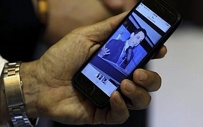 Ziad Zakka, brother of Nizar Zakka who is imprisoned in Iran, shows a photo of his brother on his cellular telephone in Beirut, Lebanon, July 18, 2017. (AP Photo/Bilal Hussein)