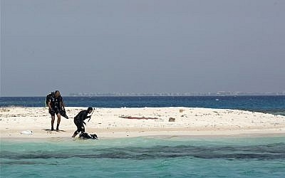 In this March 7, 2018 photo, Nouf Alosaimi, a 29-year-old female Saudi dive instructor, right, and Tamer Nasr, an Egyptian diving instructor explore a sandy island in the Red Sea after a dive, near King Abdullah Economic City, Saudi Arabia. Saudi has the longest coastline of any country along the Red Sea, and the kingdom's nascent tourism industry is betting on the clear, blue waters, coral reefs and idyllic islands off its western coastline to lure visitors from around the world. (AP Photo/Amr Nabil)